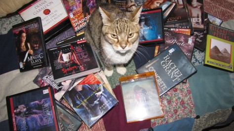 Heldig with a pile of audiobooks. She looks a little evil, does she not?